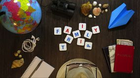 Phrase family trip on a dark wooden background with travel accessories. Stop motion.  stock video