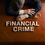 Phrase Financial Crime and devastated man. Phrase Financial Crime made of wooden block letters and devastated middle aged caucasian man in a black suit sitting stock image