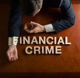 Phrase Financial Crime and devastated man. Phrase Financial Crime made of wooden block letters and devastated middle aged caucasian man in a black suit sitting stock photos