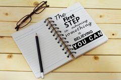 Phrase THE FIRST STEP IN ACHIEVING SOMETHING IS BELIEVING YOU CAN written on one page of a notebook. Inspirational and motivationa. Phrase THE FIRST STEP IN Royalty Free Stock Photography