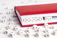 Phrase Follow us written in wooden blocks in red notebook on white wooden table. royalty free stock photo