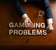 Phrase Gambling Problems and devastated man. Phrase Gambling Problems made of wooden block letters and devastated middle aged caucasian man in a black suit stock photography