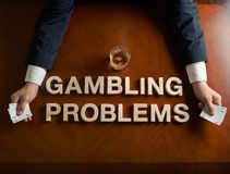 Phrase Gambling Problems and devastated man. Phrase Gambling Problems made of wooden block letters and devastated middle aged caucasian man in a black suit stock photo