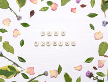 The phrase. 'good morning' on cubes in a frame of flowers, petals and green leaves on a white background.Inspirational image.Type flat, top view Royalty Free Stock Photo