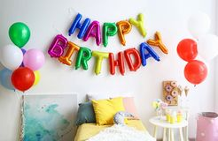 Phrase HAPPY BIRTHDAY made of colorful balloon letters and table with treats in modern