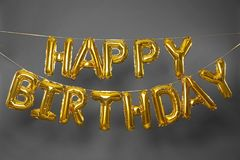Phrase HAPPY BIRTHDAY made of golden  letters on grey background