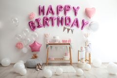 Phrase HAPPY BIRTHDAY made of pink balloon letters in room