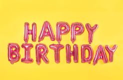 Phrase HAPPY BIRTHDAY made of pink foil balloon letters on background