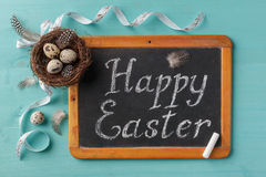 Phrase Happy Esther on chalkboard, nest with eggs Stock Photo