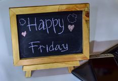 Phrase happy wednesday written on a chalkboard on it and smartphone, laptop. Phrase Happy friday written on a chalkboard on it and smartphone, laptop stock images