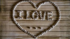The phrase `I love ...` big heart composed of white,round, plastic blocks on a wooden surface. Photo Stock Image