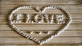 The phrase `I love ...` big heart composed of white,round, plastic blocks on a wooden surface. Photo Stock Photography
