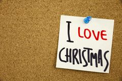 A yellow sticky note writing, caption, inscription Phrase I LOVE CHRISTMAS in black ext on a sticky note pinned to a cork notice b Royalty Free Stock Images