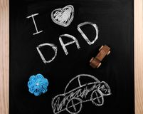 Phrase. `I love dad`, cupcake and car on chalkboard. Father`s day celebration Stock Images