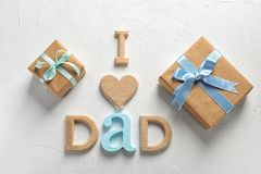 Phrase I LOVE DAD and gift boxes on light background. Father`s day celebration Stock Photos