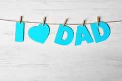 Phrase `I love dad` made of paper letters as greeting for Father`s day. On string against wooden background Royalty Free Stock Image