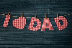 Phrase `I love dad` made of paper letters as greeting for Father`s day. On string against wooden background Stock Photography
