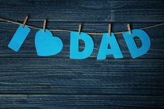 Phrase `I love dad` made of paper letters. As greeting for Father`s day on string against wooden background Royalty Free Stock Photos