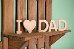 Phrase `I love dad` made of wooden letters as greeting for Father`s day. On shelf Stock Photo