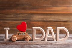 Phrase I LOVE DAD and toy car on table. Father`s day celebration Royalty Free Stock Photography