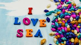 The phrase `I love sea` is composed of colorful wooden letters on a blue and white background and colorful shells. Royalty Free Stock Image