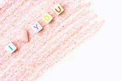 Phrase I Love You constructed from white letter cubes and pink heart shape sugar candy on red pencil strokes background on white stock photos
