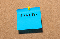 The phrase I need you written on blue sticker pinned to a cork notice board Stock Photography