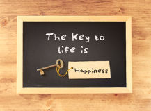The phrase the key to life is happiness written on blackboard.  Stock Image
