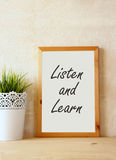The phrase listen and learn written over white drawing board against rustic textured wall Stock Photography