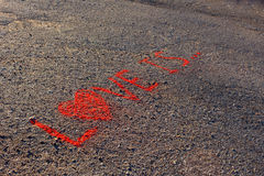 Phrase LOVE IS and three dots written on the asphalt, ground. Red color of chalk. Royalty Free Stock Photography