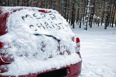 Phrase `Merry Christmas` written on snow covered car in winter forest. Space for text royalty free stock photos