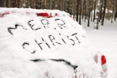Phrase `Merry Christmas` written on snow covered car in winter forest. Space for text royalty free stock photography
