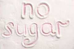 Phrase NO SUGAR written. On sugar sand royalty free stock image