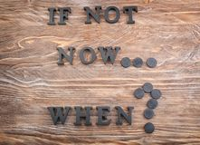 Phrase \'Is not now. When?\' composed from letters on wooden table. Time management concept royalty free stock image