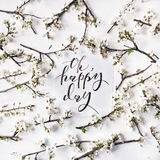 Phrase oh happy day written in calligraphy style. On paper with wreath frame with white flowers and branches  on white background. flat lay, overhead view, top Stock Photo