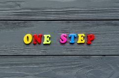 Phrase `one step` of colored plastic magnetic letters on grey wooden background. Phrase `one step` of colored plastic magnetic letters on grey wooden background Stock Photo