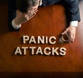 Phrase Panic Attacks and devastated man. Phrase Panic Attacks made of wooden block letters and devastated middle aged caucasian man in a black suit sitting at stock image