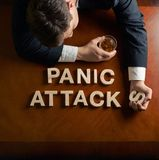 Phrase Panic Attacks and devastated man. Phrase Panic Attacks made of wooden block letters and devastated middle aged caucasian man in a black suit sitting at royalty free stock photo