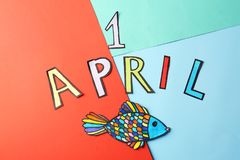 Phrase. `1 April` and paper fish on color background. Fool`s day celebration Stock Image