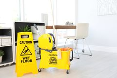 Phrase. `CAUTION WET FLOOR` on safety sign and mop bucket with cleaning supplies, indoors Royalty Free Stock Photo