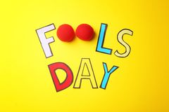 Phrase. `Fools day` and clown noses on color background. April fool`s day composition Stock Photography