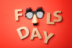 Phrase. `Fools day` and funny glasses on color background. 1st April celebration Stock Image