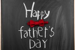 Phrase. `Happy father`s day` and bow tie on chalkboard Stock Photos