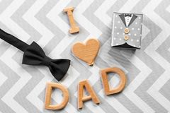Phrase. `I love dad`, bow tie and gift box on color background. Father`s day celebration Stock Photos