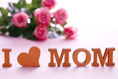 Phrase. `I LOVE MOM` made of letters and flowers on background. Happy Mother`s Day Royalty Free Stock Image