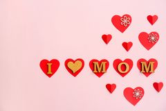 Phrase. `I LOVE MOM` made of letters and paper hearts on color background. Happy Mother`s Day Stock Photo