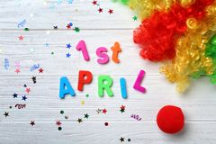 Phrase. `1st April`, clown nose and rainbow wig on wooden background. Fool`s day celebration Royalty Free Stock Image