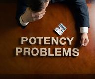Phrase Potency Problems and devastated man. Phrase Potency Problems made of wooden block letters and devastated middle aged caucasian man in a black suit sitting Stock Image