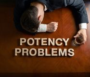Phrase Potency Problems and devastated man. Phrase Potency Problems made of wooden block letters and devastated middle aged caucasian man in a black suit sitting Royalty Free Stock Photos