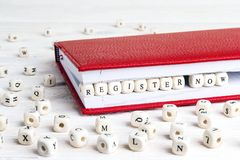 Phrase Register now written in wooden blocks in red notebook on. White wooden table. Wooden abc Stock Photo